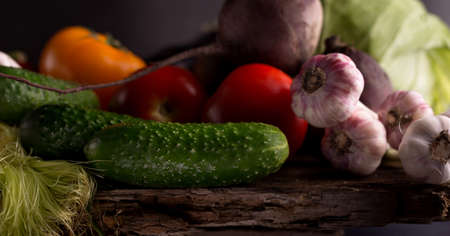 Dark moody still life of fresh vegetables on a wooden table. Healthy organic local food grocery background.