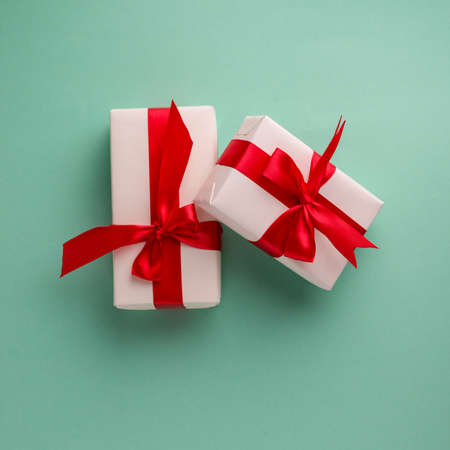 Two white gift boxes tied with bright red bows on an aqua blue background and space for text. Good for Christmas and New Year banners. Stock Photo