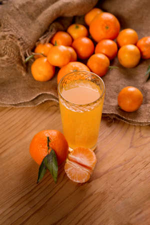 Fresh juicy tangerines or mandarins with green leaves on sack cloth and wooden table and glass of fresh juice ..