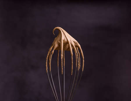 Whipped creamy instant coffee on a whisk close-up. How to cook the Dalgona Coffee process Reklamní fotografie