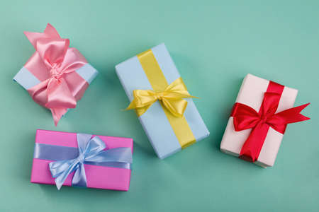 Different gift boxes with red, yellow. and blue bows on turquoise color background. Mother's day or minimalism concept to sale company