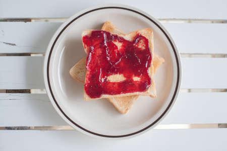 comiendo pan: vista superior de cerca de una rebanada de pan tostado con mermelada en la mesa de madera Foto de archivo
