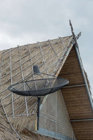 roofing system: satellite dish on  thatched roof