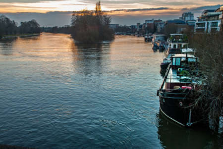 many House boats are beached on the side of the River Thames at sunset