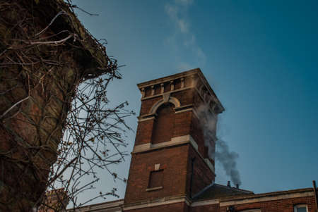 Smoke from brick chimney on the roof against the blue sky Foto de archivo