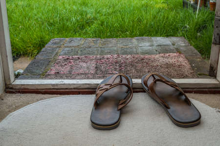 Mens sandals on a white carpet near the door Reklamní fotografie