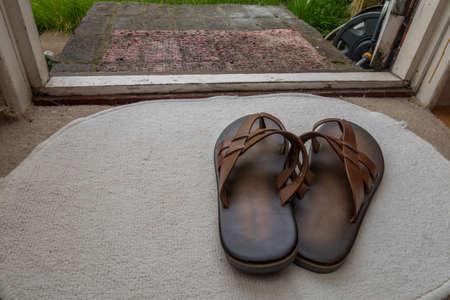 Men's sandals on a white carpet near the door