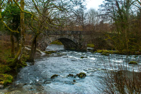 View of the traditional stone bridge With beautiful flowing stream below. Stock Photo - 121549922