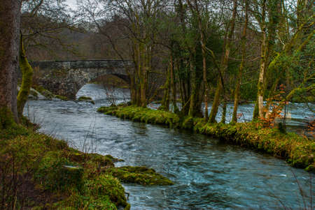 View of the traditional stone bridge With beautiful flowing stream below. Stock Photo - 121549929