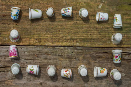 Eighteen Vintage thimbles on an Old wooden floor. concept with copy space. Archivio Fotografico