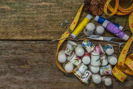 Spools of thread and basic sewing tools including pins, needle, a thimble, and tape measure on an old wooden tabletop. concept with copy space. Stock Photo