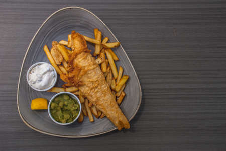 British Traditional Fish and chips with mashed peas, tartar sauce on a wooden table, Top view