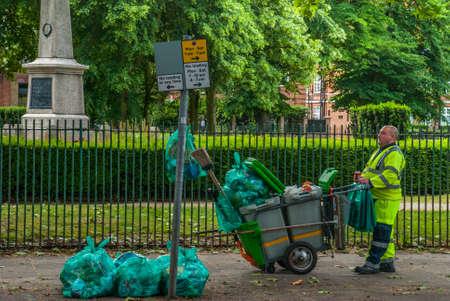 London - 5 May 2019 London street-sweeper and trash cart.