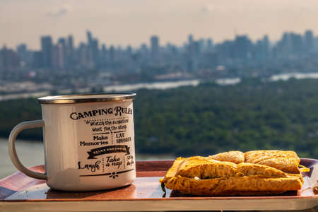 Breakfast - sandwiches and coffee on a wooden tray with natural views. Stock Photo