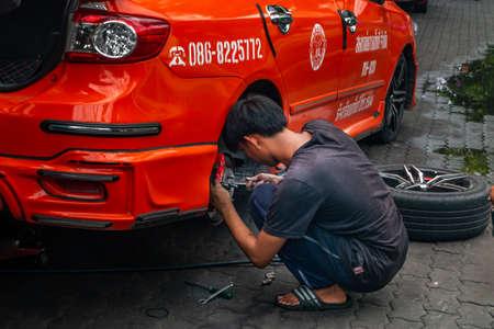 bangkok,Thailand - jun 29, 2019 : A mechanic in a black T-shirt is sitting repairing the wheel hub orange taxi car At the front of the garage.