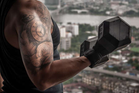 Closeup of Strong bodybuilder, power athletic man in training pumping up muscles with dumbbell in gym or fitness club.