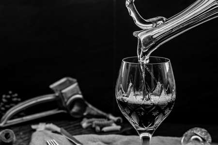 Black and white picture of Pouring red wine from pitcher into the wineglass : traditional winemaking and wine tasting concept, Free space for text.