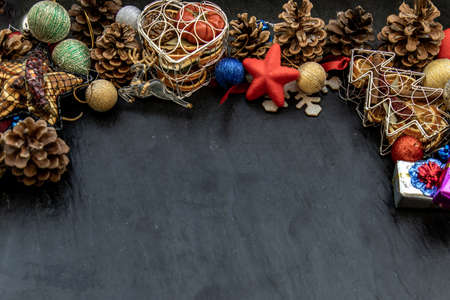 Wide arch shaped Christmas decoration border. Twigs christmas tree, brown natural pine cones and and Xmas deer with variety of fruits on dark background, Copy space.