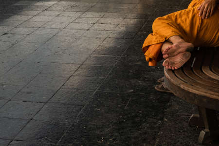 Bangkok, thailand - Jul 7, 2019 : A monk is sleep on wooden chairs are waiting for trains in the area provided at Main railway station of Hua Lamphong, Selective focus.