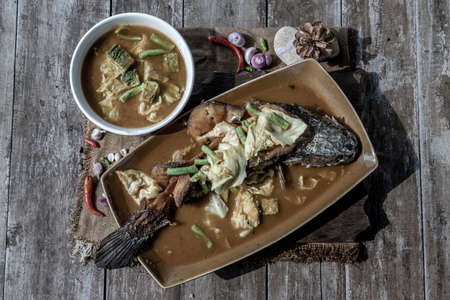 Deep fried whole Snakehad fish topped with Acacia omelets in vegetable sour soup (Orange curry with Cha-om).