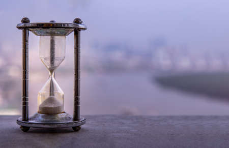 Hourglass with blur city at evening time. Beauty and past moments concepts with copy space. vintage style Reklamní fotografie