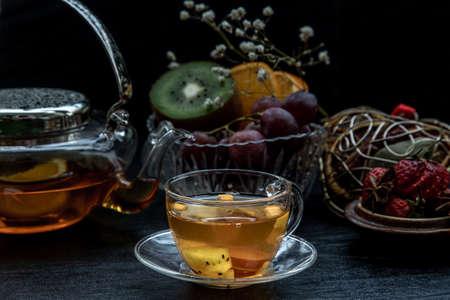 Glass of freshly brewed fruit and herbal tea. Darker background.