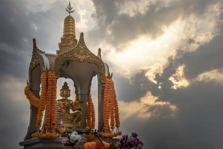 Golden statue of Phra Phrom or four-faced Buddha in beautiful sky. Four-faced Buddha regarded in Thai culture as deity of good fortune and protection. Selective focus.