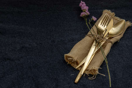 A set of bronze cutlery, spoon, fork and knife black background. Copy space, Selective focus.