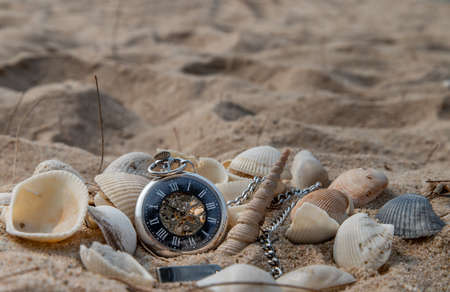 Antique pocket watch and shells in sand on the beach and copy space. Time of life in nature concept. Selective focus. 版權商用圖片