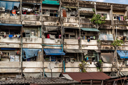 Bangkok, Thailand - Nov 23, 2019 : Geometrical pattern of multistory apartment house with group of windows and tenant lumber on balconies, Slum house, Social problems in overcrowded countries.