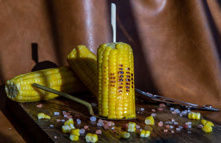 Grilled corn on the cob  on rustic wooden board over brown leather background.  Ideas for barbecue and grill parties, Barbecue concept. Banque d'images - 150385317