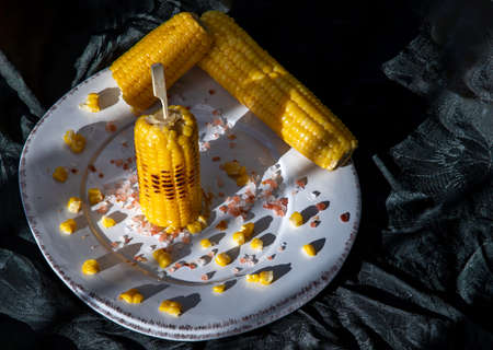 Grilled corn on the cob  on classic white plate over dark background. Ideas for barbecue and grill parties, Barbecue concept.