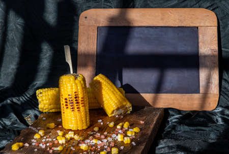 Grilled corn on the cob  on rustic wooden board   over dark background and Free space for text. Ideas for barbecue and grill parties, Barbecue concept.