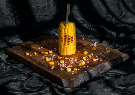 Grilled corn on the cob  on rustic wooden board   over dark background. Ideas for barbecue and grill parties, Barbecue concept. Banque d'images - 150623471