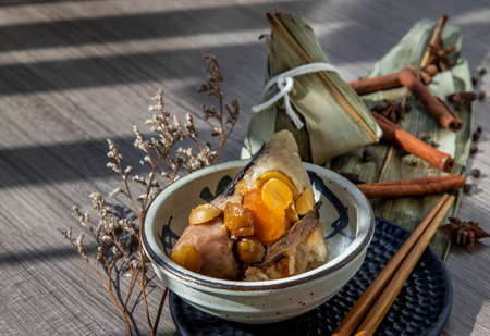 Chinese rice dumplings (Zongzi) shaped pyramidal wrapped by leaves ingredients on bowl chinese style and chopsticks. Famous asian tasty handmade food in dragon boat (duan wu) festival occasion. 写真素材