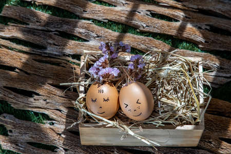 The two happy eggs is lying on dry straw. Happy and relaxing concept.