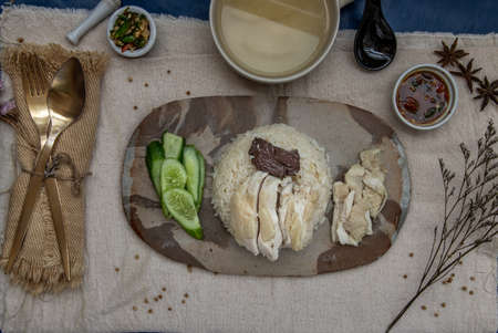 Hainanese chicken rice (Steam chicken with rice) with cucumber closeup on a plate and broth. Horizontal top view. Фото со стока