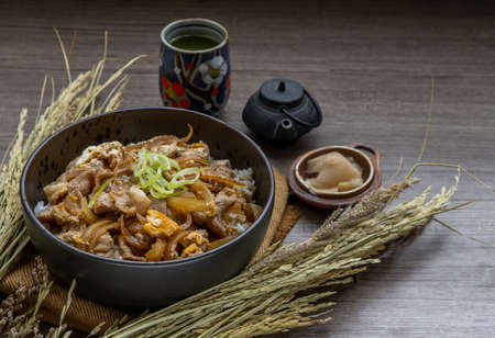 Japanese pork rice bowl with egg and onion (Donburi) served with pickled ginger and green tea on wooden table. Japanese food style.