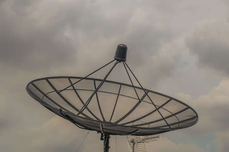 Black Satellite Dish Antenna Receiver Against on Blue Sky background for Communication and Media Industry, Symbolizing Global Communications. Free copy space for text, Selective focus.