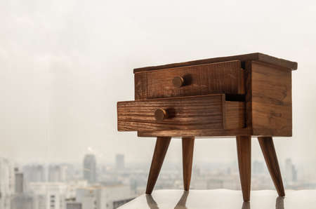 Teak bedside table. Modern designer nightstand, Cabinet with two drawers, House room interior, Selective focus.