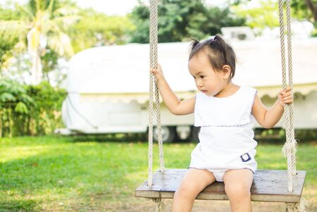Thailands two years of age are playing the swings.