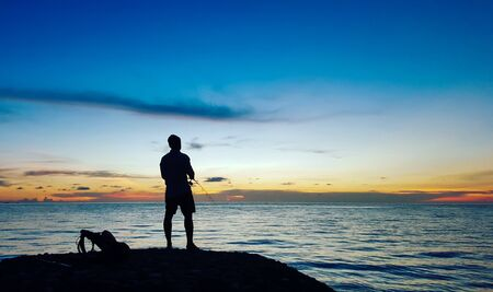 Fishermen standing on the rocks at sunrise on koh Chang thailand