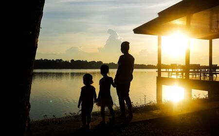 Lady and children stand by the lake in the evening