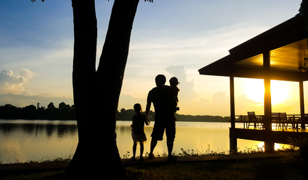 Man and children stand by the lake in the evening