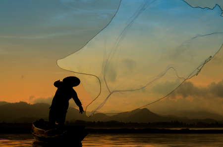 entrapment: Fisherman in action when cast a net in Bangpra lake at draw, Thailand. Stock Photo