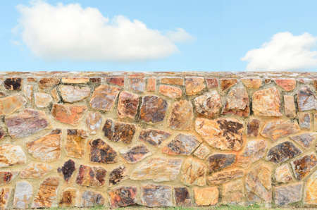 Stone wall background and blue sky