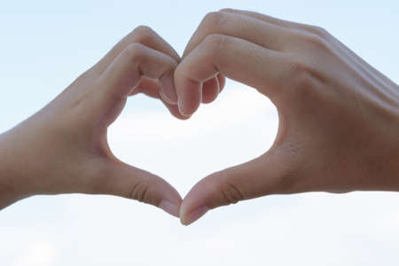 a newly married couple: clasped hands forming a heart with natural background