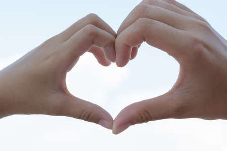 clasped: clasped hands forming a heart with natural background
