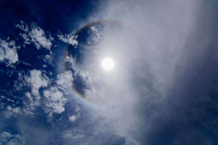 Sun corona on blue sky with clouds Stock Photo