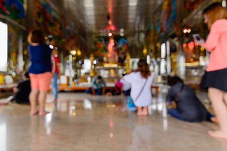 oneself: People prostrate oneself to worship Buddha in church, Focus of blur